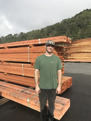 Man standing in front of stacks of wood
