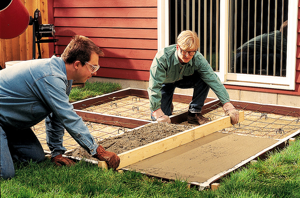 Two men floating concrete for an outdoor patio.
