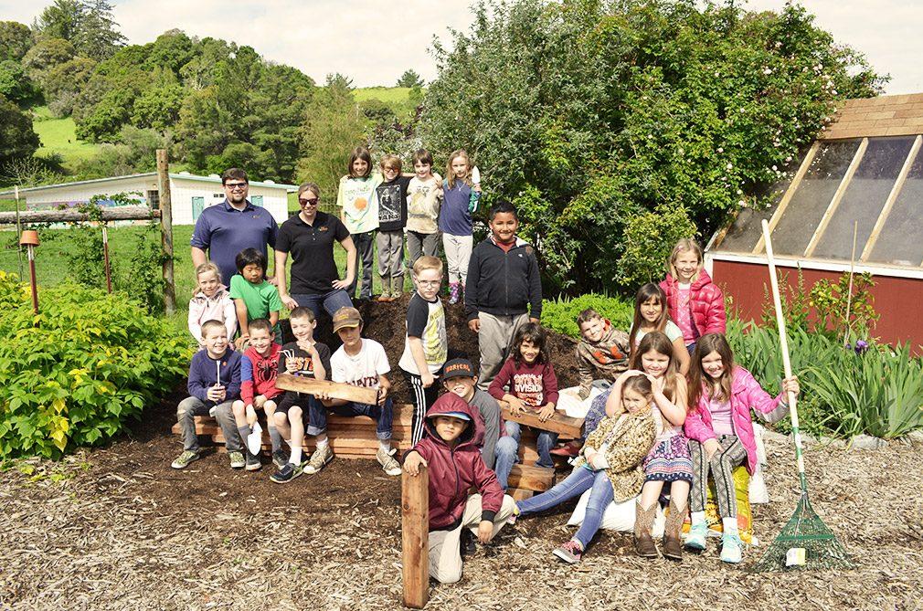Children with garden bed donation.