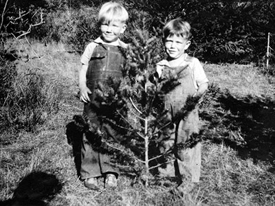 Two young boys standing in back of a sapling