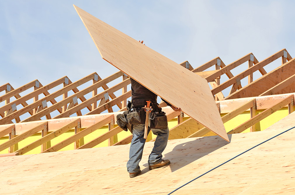 Contractor placing a sheet of plywood on a roof