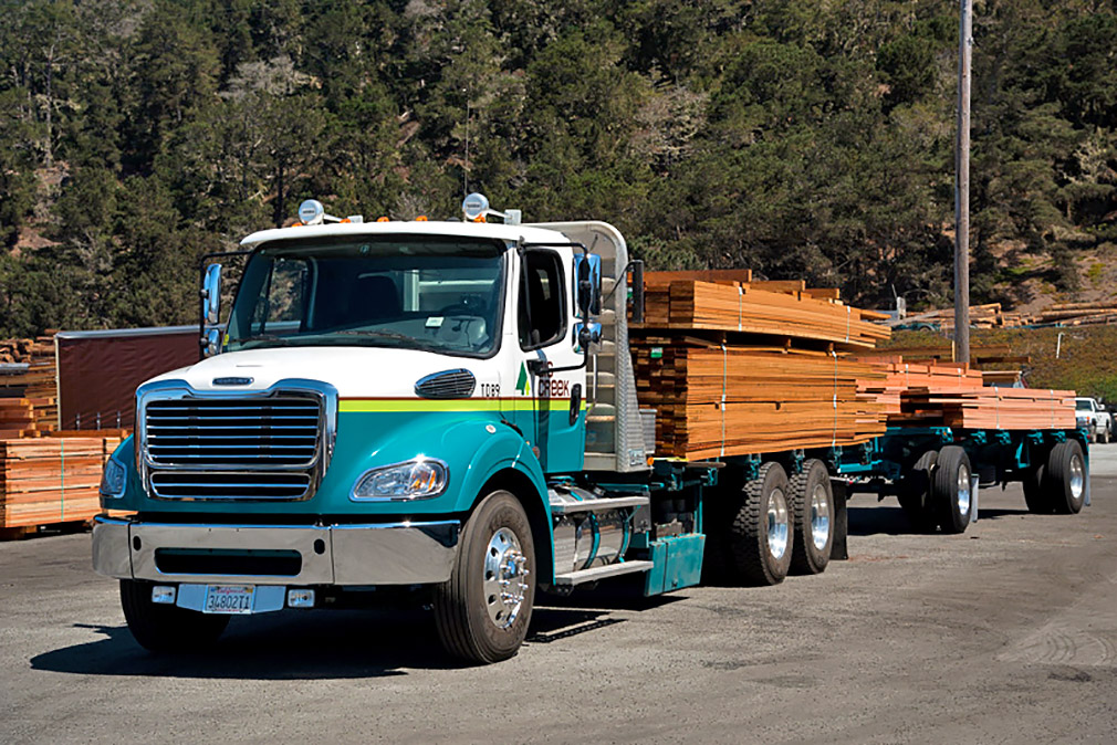 Flatbed truck and trailer with redwood boards.