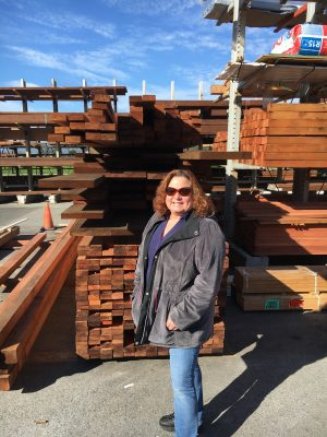 Woman standing in front of a unit of lumber