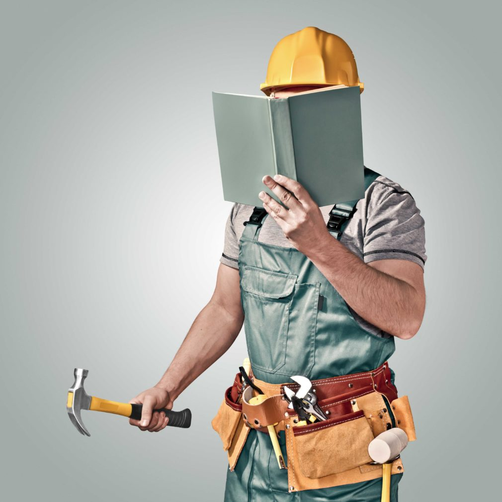 Contractor with hammer reading a book