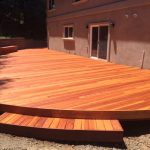 Curved redwood deck with step.