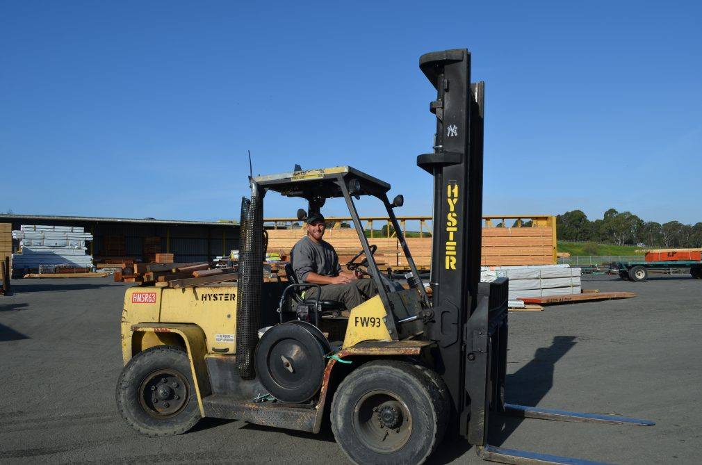 Man sitting on forklift in front of a stack of lumber