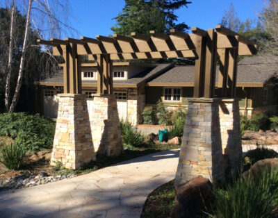 Wood and stone trellis leading entry path to a house