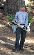 Man in forest holding logging tools.