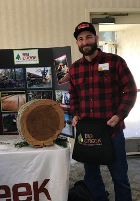 Customer standing in front of prize and redwood round