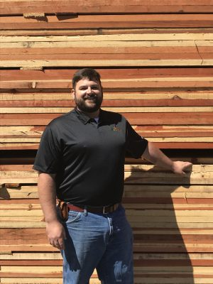 Man Standing In Fromt of Lumber