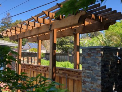 Backyard wood trellis with stone work and some greenery
