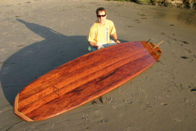 Man with redwood surfboard on the beach