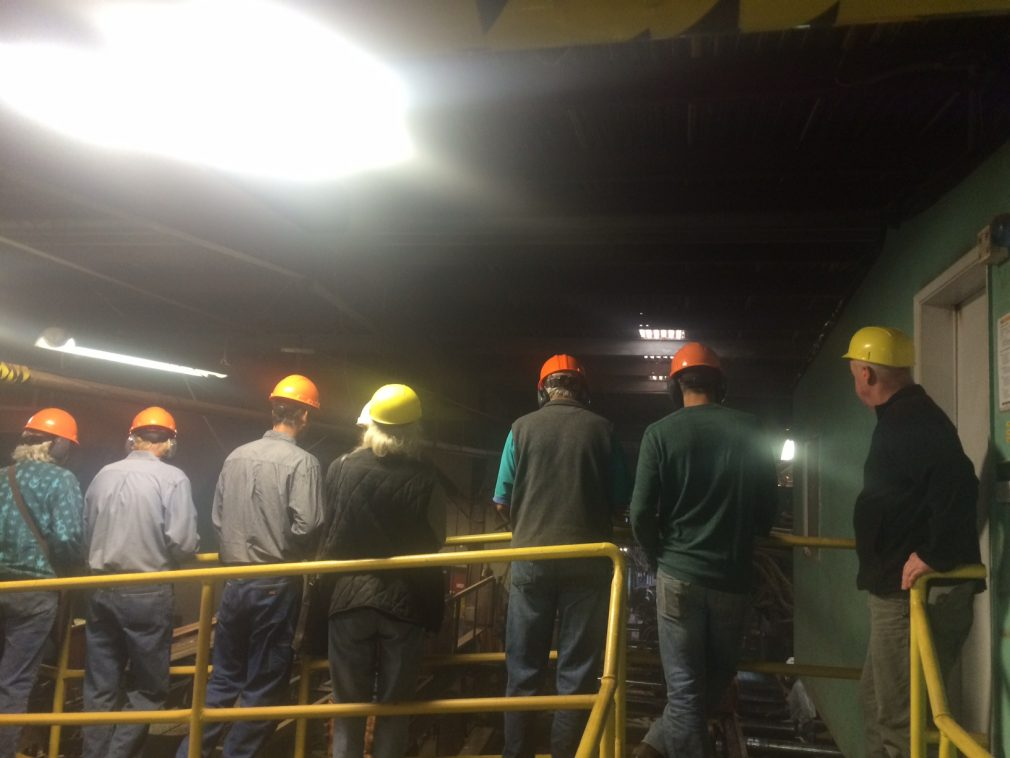 People with hardhats touring sawmill
