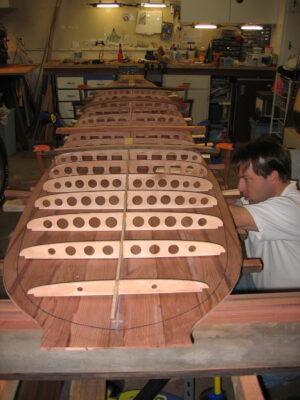 Man building a redwood surfboard
