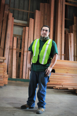Man in Safety Vest Standing in front of Lumber