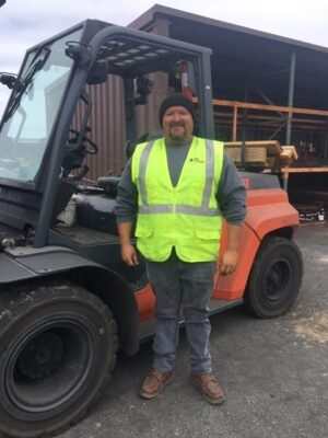 Man in safety vest standing in front of fork lift