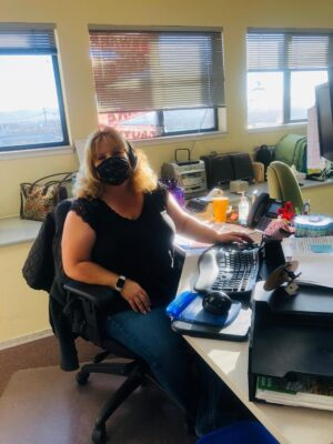 lady sitting at her desk with her mask on