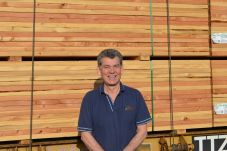 Employee in front of lumber.