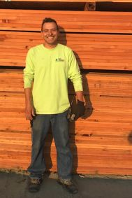 Man in yellow shirt standing in front of lumber.
